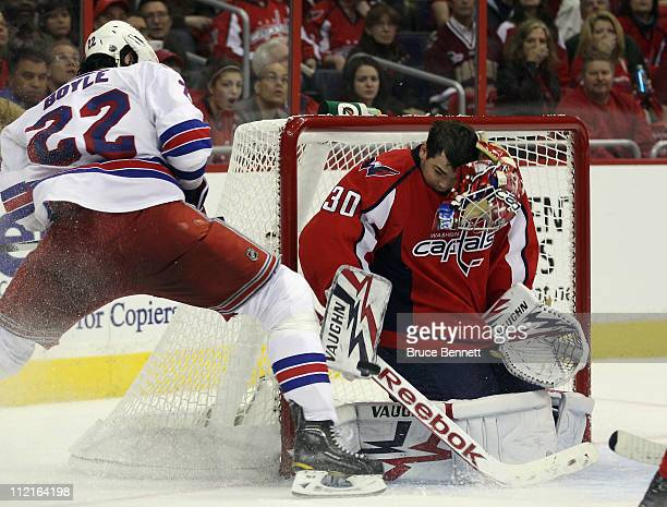 Goaltender Michal Neuvirth of the Washington Capitals loses his mask in his game against Brian Boyle and the New York Rangers in Game One of the...