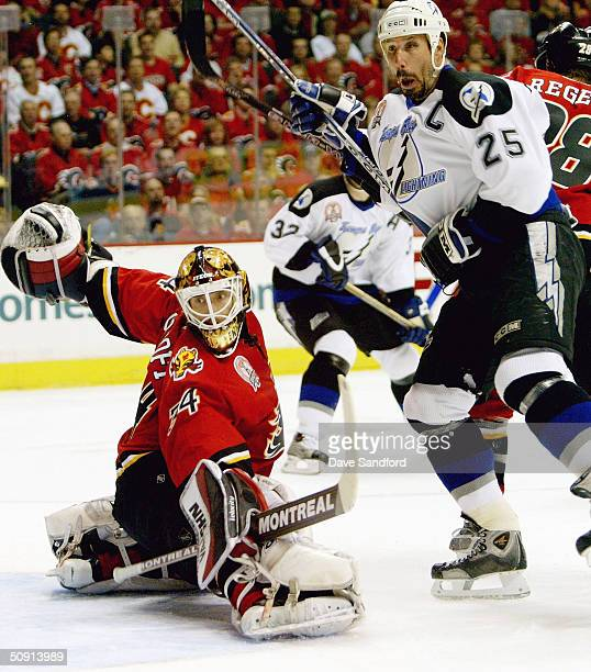 Goaltender Miikka Kiprusoff of the Calgary Flames and Dave Andreychuk of the Tampa Bay Lightning watch a shot on goal go wide in game four of the NHL...
