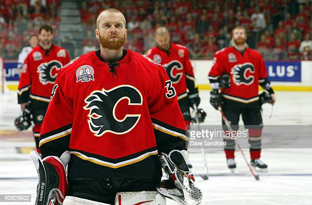 Goaltender Miikka Kiprusoff of the Calgary Flames and the rest of the Flames team stand during the singing of the National Anthem before the start of...