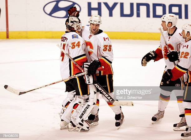 Goaltender Miikka Kiprusoff of the Calgary Flames celebrates a win with teammate Adrian Aucoin after a shoot out against the Florida Panthers at the...