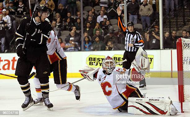 Goaltender Miikka Kiprusoff of the Calgary Flames makes a save in front of James Neal of the Dallas Stars in the third period at American Airlines...