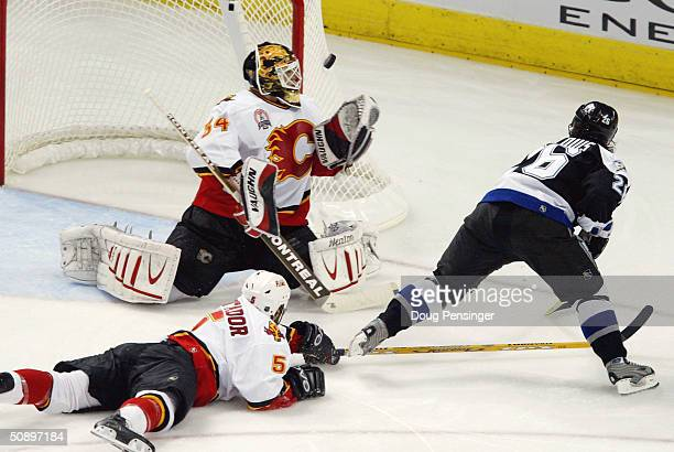 Goaltender Miikka Kiprusoff of the Calgary Flames makes a save on a shot by Martin St Louis of the Tampa Bay Lightning as teammate Steve Montador...
