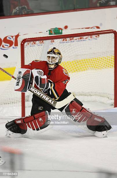 Goaltender Miikka Kiprusoff of the Calgary Flames makes a save against the San Jose Sharks during the NHL game at Pengrowth Saddledome on October 9...