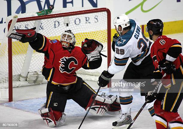 Goaltender Miikka Kiprusoff of the Calgary Flames swats the puck out of thre air on a shot by Ryane Clowe of the San Jose Sharks as Cory Sarich of...