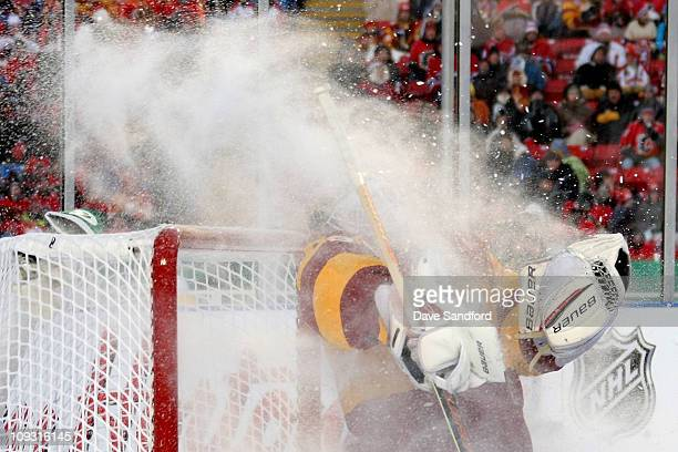 Goaltender Miikka Kiprusoff of the Calgary Flames takes a maskful of ice from the Travis Moen of the Montreal Canadiens in the second period during...