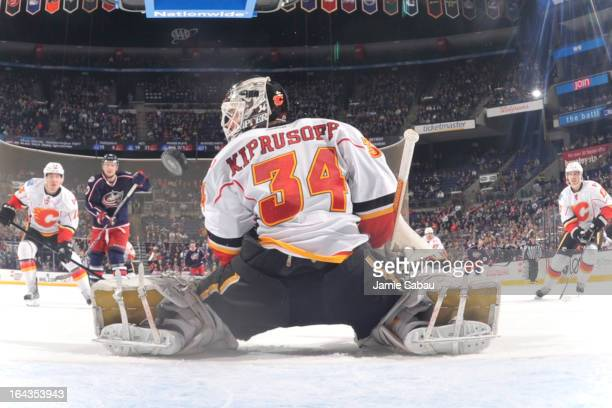 Goaltender Miikka Kiprusoff of the Calgary Flames watches as a shot from Colton Gillies of the Columbus Blue Jackets goes into the net during the...
