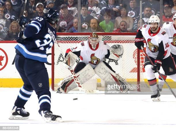 Goaltender Mike Condon and Tom Pyatt of the Ottawa Senators keep an eye on the point as Dustin Byfuglien of the Winnipeg Jets takes a shot during...