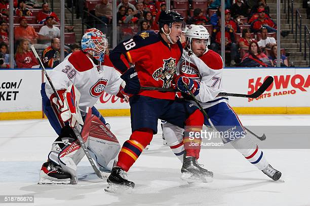 Goaltender Mike Condon defends the net as Joel Hanley of the Montreal Canadiens checks Reilly Smith of the Florida Panthers away from the crease...