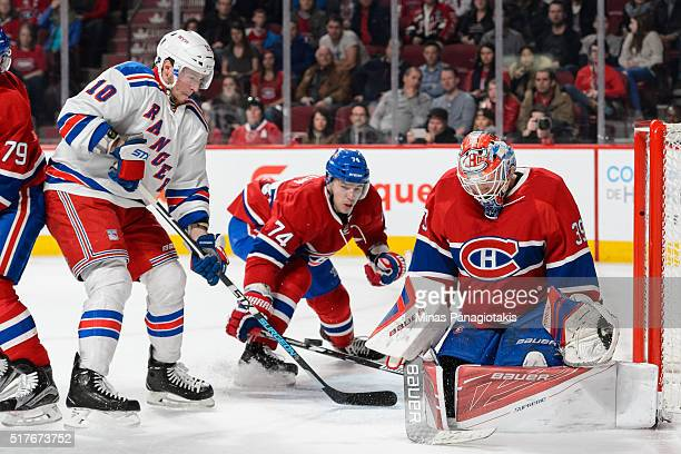 Goaltender Mike Condon of the Montreal Canadiens and teammate Alexei Emelin try to defend the puck against JT Miller of the New York Rangers during...