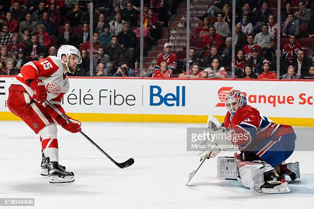Goaltender Mike Condon of the Montreal Canadiens gloves the puck on a shot by Riley Sheahan of the Detroit Red Wings during the NHL game at the Bell...