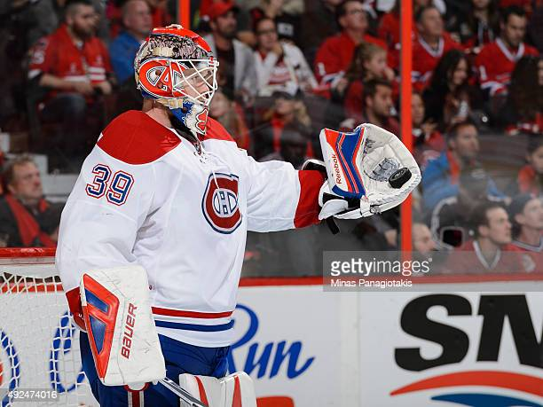 Goaltender Mike Condon of the Montreal Canadiens holds out his glove in his first NHL game against the Ottawa Senators and records his first career...