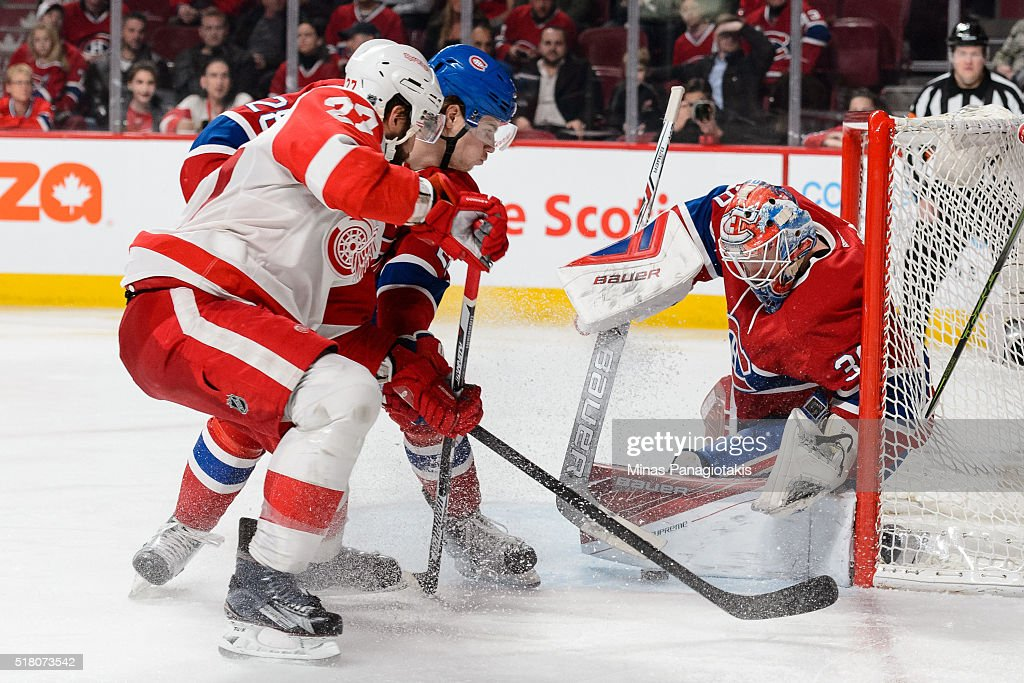 Goaltender Mike Condon #39 of the Montreal Canadiens makes a pad save while teammate Nathan Beaulieu #28 defends against Kyle Quincey #27 of the Detroit Red Wings during the NHL game at the Bell Centre on March 29, 2016 in Montreal, Quebec, Canada. The Montreal Canadiens defeated the Detroit Red Wings 4-3.