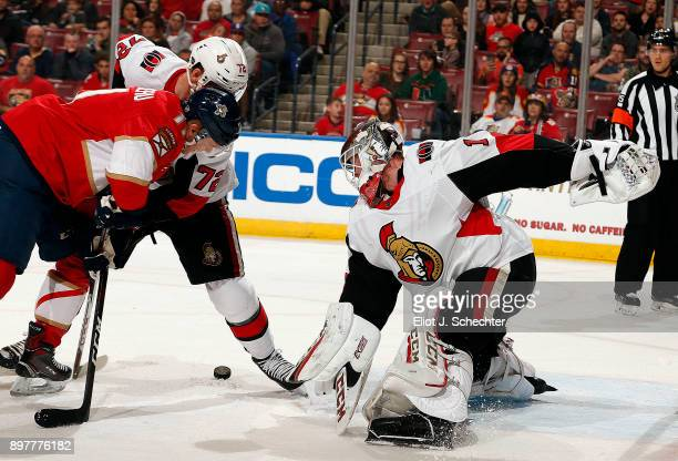 Goaltender Mike Condon of the Ottawa Senators defends the net with the help of teammate Thomas Chabot against Jonathan Huberdeau of the Florida...