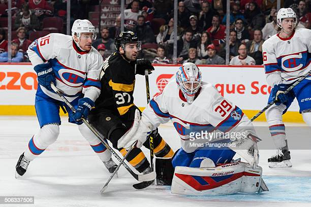Goaltender Mike Condon watches the puck while Tomas Fleischmann of the Montreal Canadiens and Patrice Bergeron of the Boston Bruins battle for...