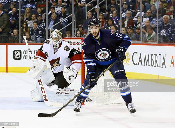 Goaltender Mike Smith of the Arizona Coyotes and Drew Stafford of the Winnipeg Jets keep an eye on the play during first period action at the MTS...