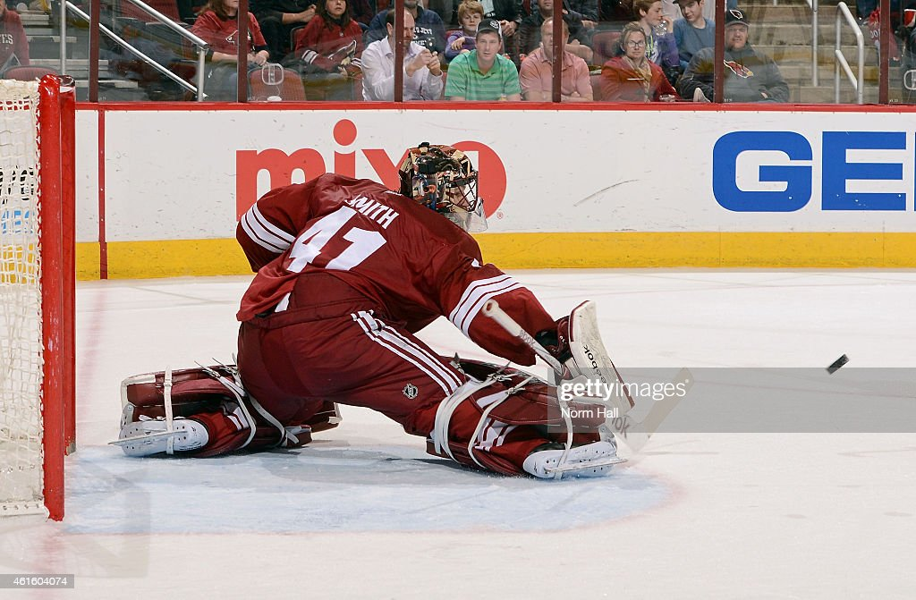 Goaltender Mike Smith #41 of the Arizona Coyotes deflects the puck away on a save against the Calgary Flames during the third period at Gila River Arena on January 15, 2015 in Glendale, Arizona.