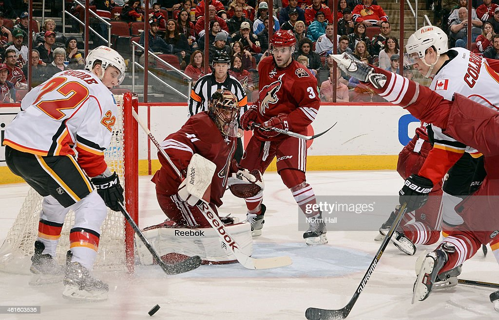 Goaltender Mike Smith #41 of the Arizona Coyotes deflects the puck between Drew Shore #22 and Joe Colborne #8 the Calgary Flames during the third period at Gila River Arena on January 15, 2015 in Glendale, Arizona.