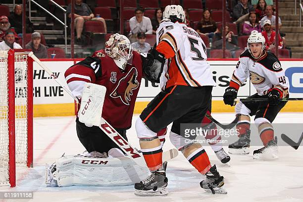 Goaltender Mike Smith of the Arizona Coyotes makes a glove save as Nick Sorensen and Michael Sgarbossa of the Anaheim Ducks skate in during the...