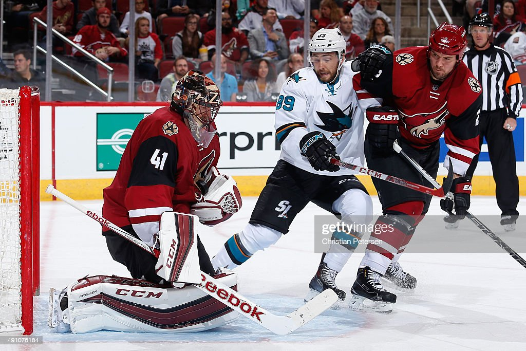 Goaltender Mike Smith #41 of the Arizona Coyotes makes a glove save on a shot as Barclay Goodrow #89 of the San Jose Sharks skates in during the third period of the NHL preseason game at Gila River Arena on October 2, 2015 in Glendale, Arizona. The Sharks defeated the Coyotes 3-0.