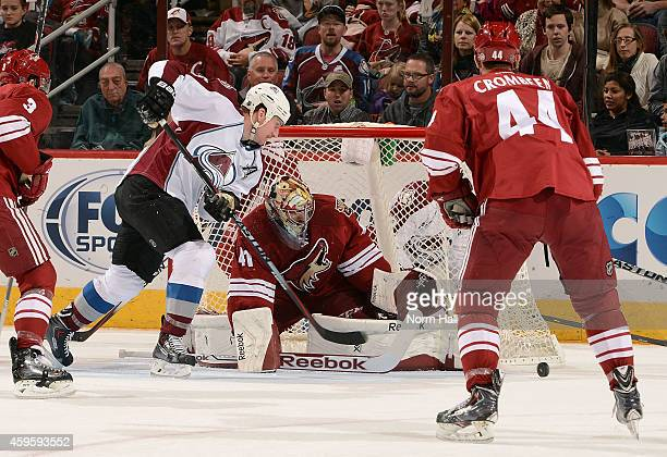 Goaltender Mike Smith of the Arizona Coyotes makes a save as Cody McLeod of the Colorado Avalanche skates for the rebound during the second period at...