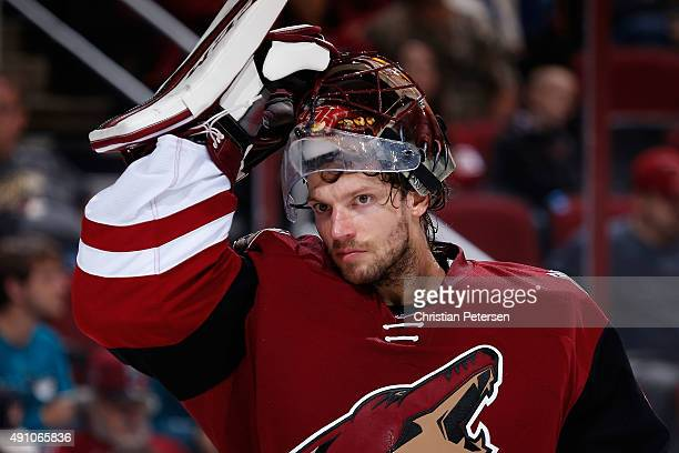Goaltender Mike Smith of the Arizona Coyotes puts on his mask during the second period of the NHL preseason game against the San Jose Sharks at Gila...