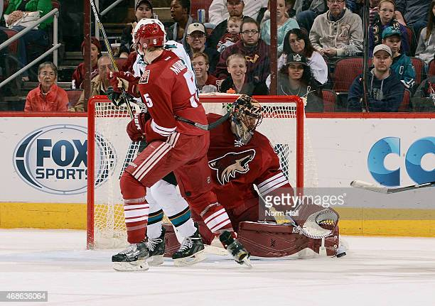 Goaltender Mike Smith of the Arizona Coyotes reaches out to glove the puck as Patrick Marleau of the San Jose Sharks and Connor Murphy of the Coyotes...