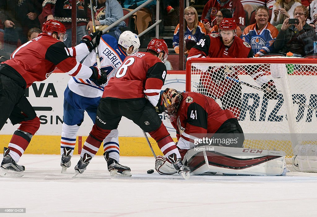 Goaltender Mike Smith #41 of the Arizona Coyotes tries to cover the puck as Martin Hanzal #11 and Tobias Rieder #8 of the Coyotes battle in front of the net with Jordan Eberle #14 of the Edmonton Oilers during the third period at Gila River Arena on November 12, 2015 in Glendale, Arizona.