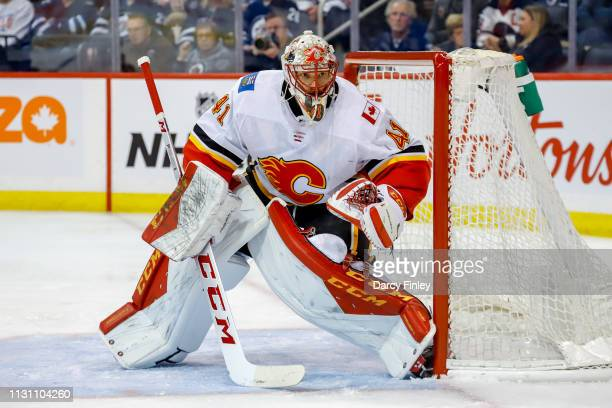 Goaltender Mike Smith of the Calgary Flames guards the net during first period action against the Winnipeg Jets at the Bell MTS Place on March 16...