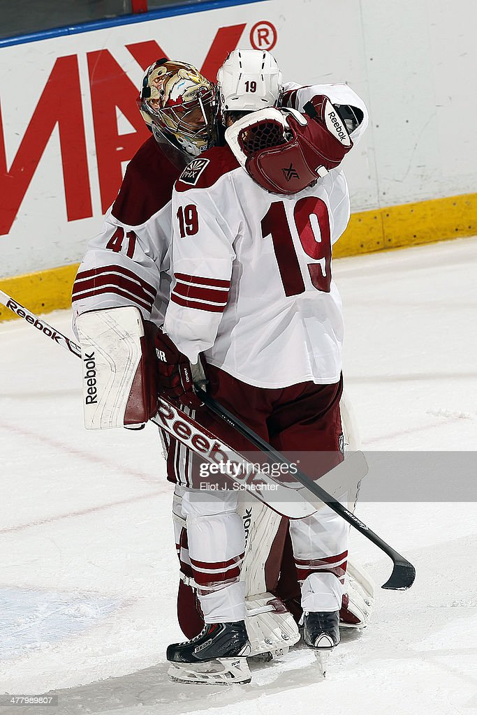 Goaltender Mike Smith #41 of the Phoenix Coyotes hugs teammate Shane Doan #19 after a 3-1 win against the Florida Panthers at the BB&T Center on March 11, 2014 in Sunrise, Florida.