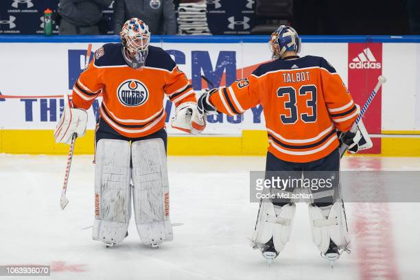 Goaltender Mikko Koskinen bumps fists with goaltender Cam Talbot of the Edmonton Oilers during warm up against the Minnesota Wild at Rogers Place on...