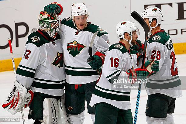 Goaltender Niklas Backstrom of the Minnesota Wild celebrates with teammate Charlie Coyle their 41 win against the Florida Panthers at the BBT Center...