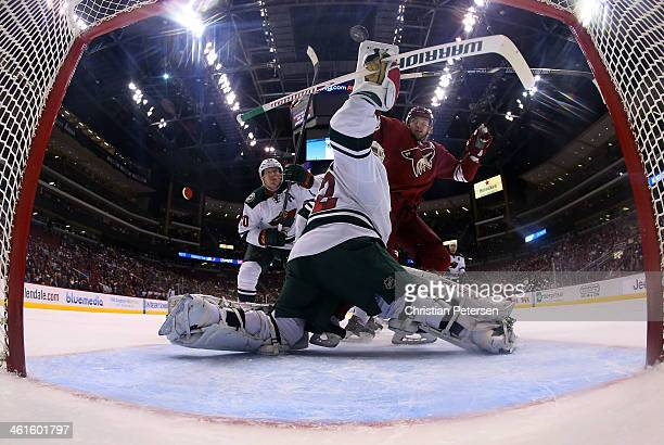 Goaltender Niklas Backstrom of the Minnesota Wild turns to make a play on the puck as Martin Hanzal of the Phoenix Coyotes skates in alongside Ryan...