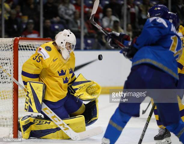 Goaltender Olle Eriksson of Sweden makes a save in the first period on Baatyrlan Muratov of Kazakhstan at the IIHF World Junior Championships at the...