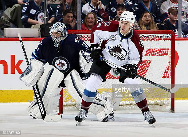 Goaltender Ondrej Pavelec of the Winnipeg Jets and Shawn Matthias of the Colorado Avalanche keep an eye on the play during third period action at the...