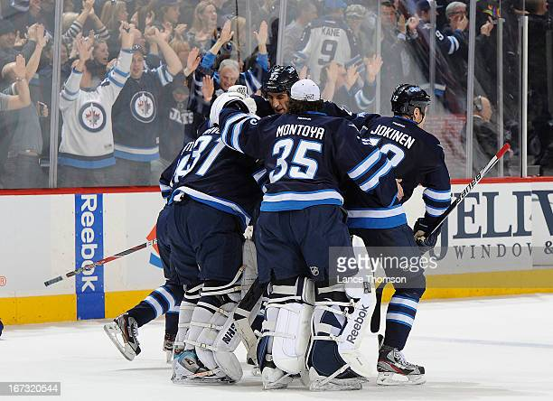 Goaltender Ondrej Pavelec of the Winnipeg Jets gets congratulated by teammates Chris Thorburn Olli Jokinen and Al Montoya after backstopping the Jets...