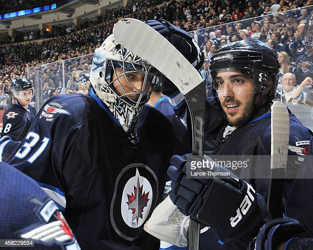 Goaltender Ondrej Pavelec of the Winnipeg Jets gets congratulated by teammate Mathieu Perreault after backstopping the Jets to a 21 overtime victory...