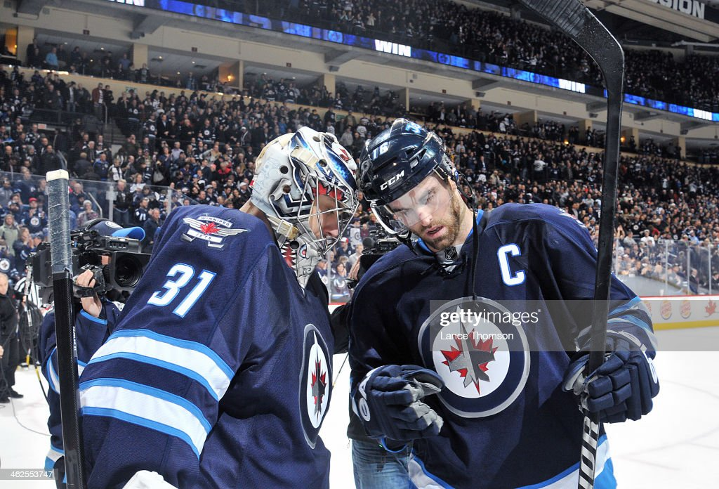 Goaltender Ondrej Pavelec #31 of the Winnipeg Jets gets congratulated by teammate Andrew Ladd #16 after backstopping the Jets to a 5-1 victory over the Phoenix Coyotes at the MTS Centre on January 13, 2014 in Winnipeg, Manitoba, Canada.