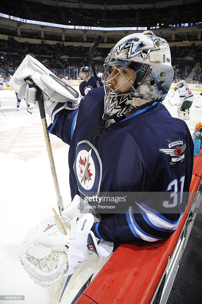Goaltender Ondrej Pavelec #31 of the Winnipeg Jets looks on during the pre-game warm up prior to NHL action against the Minnesota Wild at the MTS Centre on April 7, 2014 in Winnipeg, Manitoba, Canada.