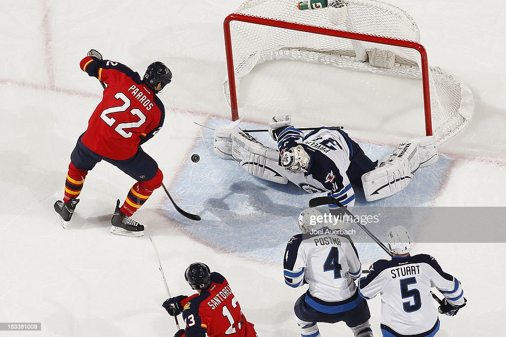 Goaltender Ondrej Pavelec #31 of the Winnipeg Jets stops a shot by George Parros #22 of the Florida Panthers during second period action at the BB&T Center on March 8, 2013 in Sunrise, Florida. The Jets defeated the Panthers 3-2 in overtime.