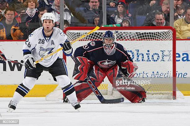 Goaltender Pascal Leclaire of the Columbus Blue Jackets defends the net as Martin St. Louis of the Tampa Bay Lightning camps out in front waiting for...