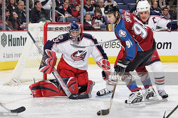 Goaltender Pascal Leclaire of the Columbus Blue Jackets keeps his eyes on the puck as Ryan Smyth of the Colorado Avalanche skates with the puck in...
