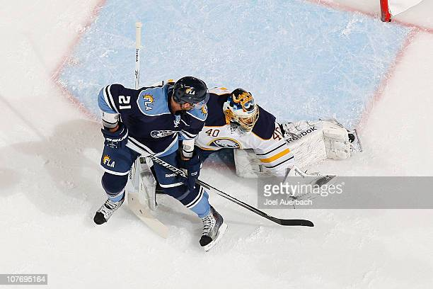 Goaltender Patrick Lalime of the Buffalo Sabres makes a glove save as Christopher Higgins of the Florida Panthers waits for a rebound on December 17,...