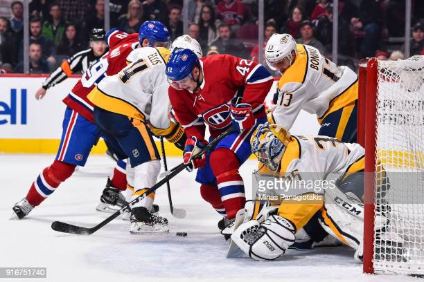 Goaltender Pekka Rinne of the Nashville Predators defends his net as teammate Nick Bonino challenges Byron Froese of the Montreal Canadiens during...