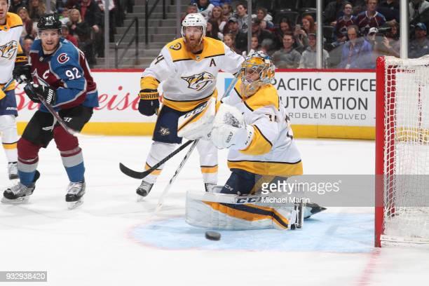Goaltender Pekka Rinne of the Nashville Predators deflects a shot beside teammate Ryan Ellis and Gabriel Landeskog of the Colorado Avalanche at the...