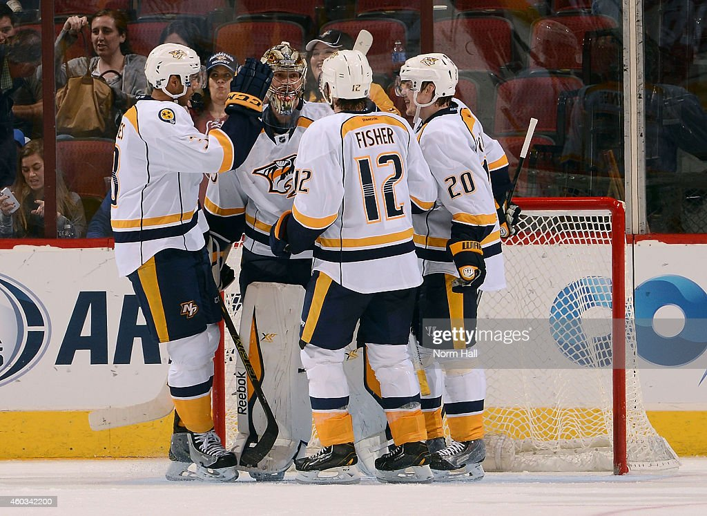 Goaltender Pekka Rinne #35 of the Nashville Predators is congratulated by teammates Seth Jones #3, Mike Fisher #12 and Anton Volchenkov #20 after a 5-1 victory against the Arizoan Coyotes at Gila River Arena on December 11, 2014 in Glendale, Arizona.