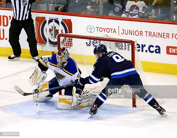 Goaltender Pheonix Copley of the St Louis Blues and Andrew Copp of the Winnipeg Jets battle for the puck during second period action at the MTS...
