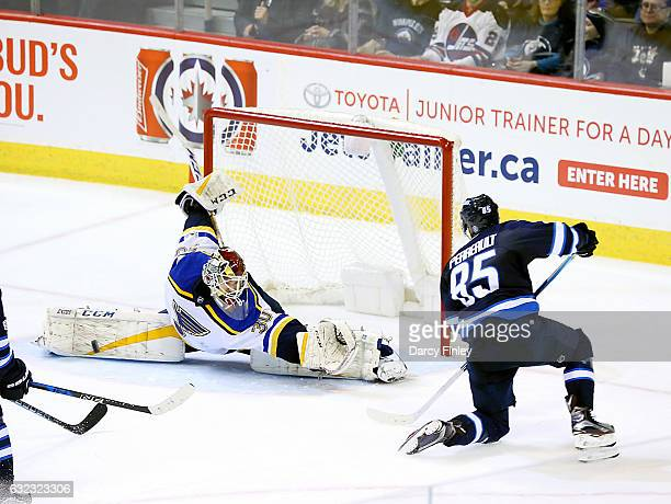 Goaltender Pheonix Copley of the St Louis Blues does the splits as he makes a pad save on Mathieu Perreault of the Winnipeg Jets during second period...