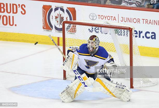 Goaltender Pheonix Copley of the St Louis Blues keeps an eye on the flying puck during second period action against the Winnipeg Jets at the MTS...