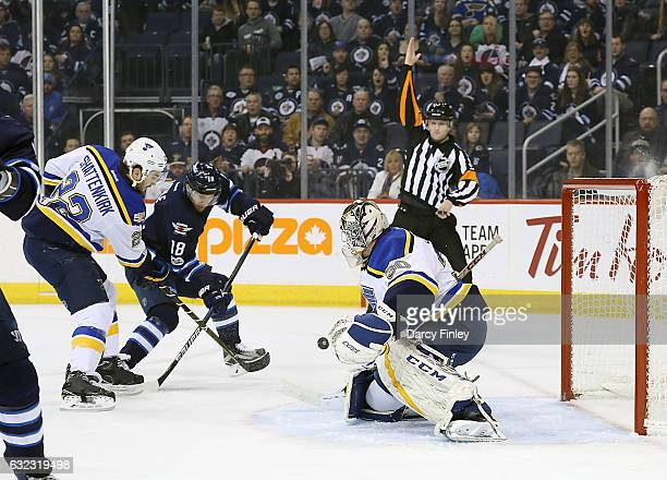 Goaltender Pheonix Copley of the St Louis Blues slides across the crease as teammate Kevin Shattenkirk battles Bryan Little of the Winnipeg Jets for...