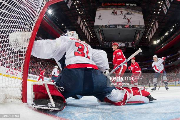 Goaltender Philipp Grubauer of the Washington Capitals reaches out for the puck as teammate John Carlson defends against Dylan Larkin and Tyler...